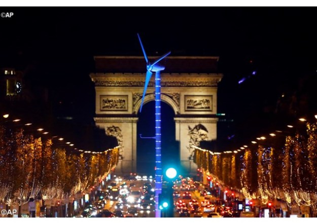 A power-generating wind turbine is seen on the Champs Elysees avenue with the Arc de Triomphe in background as part of COP21. – AP