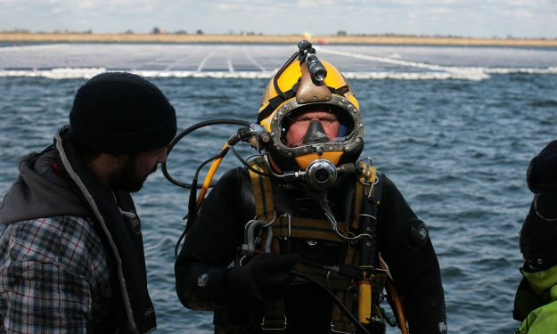 Divers fix anchors onto the bed of the reservoir. Photograph: Martin Godwin for the Guardian