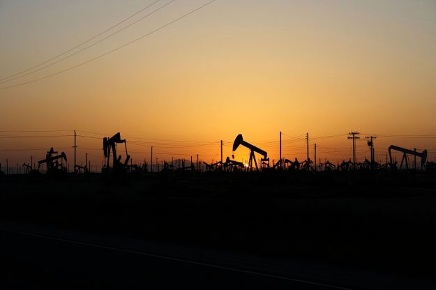 Sun setting on oil field (Photo by Arne Hückelheim, Wikimedia Commons)